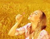 女孩在麦田上吹肥皂泡泡 — 图库照片