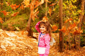 Sweet little girl in autumn forest — Stock Photo
