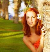 Cute girl near palm tree — Stock Photo