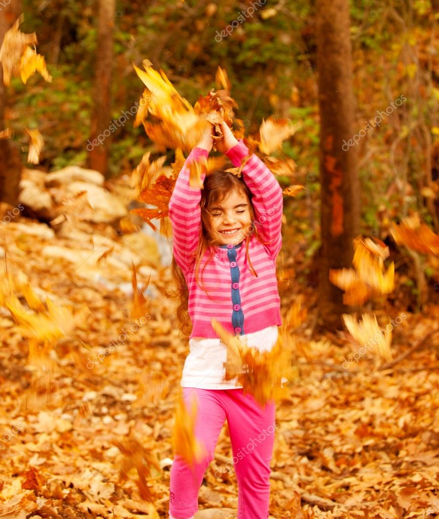Picture of cheerful little girl playing outdoors, sweet small female child throwing up dry yellow fall foliage and laughing with closed eyes, nice baby in autumn woo — Stock Photo #13684492