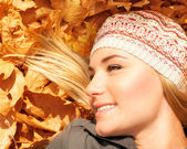 Cute blonde laying down on tree leaves — Stock Photo
