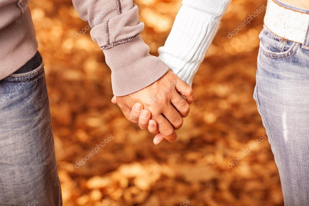 Photo of two loving holding each other by hands on golden autumnal background, romantic relationship, best friends, happy couple, orange fall foliage under fe — Stock Photo #14043186