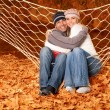Young family hugging in hammock - Stock Photo
