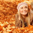 Girl lying down on autumnal leaves - Stock Photo