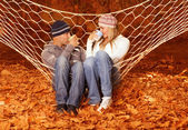 Young couple drink tea in hammock — Stock Photo