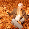 Girl throwing up autumnal leaves - Stock Photo