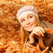 Pretty woman on autumnal leaves — Stock Photo