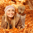 Постер, плакат: Woman lay down on autumnal foliage