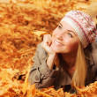 Cheerful teen on fall foliage - Stock Photo