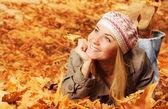 Sonbaharda yapraklar üzerinde neşeli teen — Stok fotoğraf