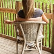 Rear view of girl sitting on veranda - Stock Photo