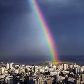 Bright rainbow over city — Stock Photo
