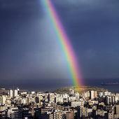 Heldere regenboog over stad — Stockfoto