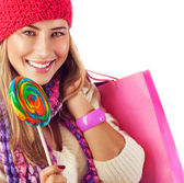 Girl lick sweets and holding pink bag — Stock Photo