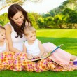 Mother with children read book — Stockfoto