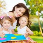 Happy family reading book — Stock Photo