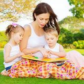 маленькие дети с мама читать книгу — Стоковое фото