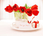 Red tulips and cup of tea — Stock Photo
