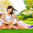 Woman with daughter and son read fairytale - Stok fotoğraf