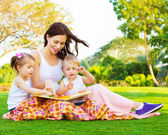 Woman with daughter and son read fairytale — Foto Stock