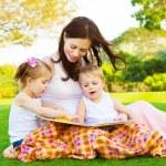 Happy family reading outdoors — Stock Photo