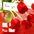 Red tulips with postcard - Stock Photo