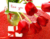 Red tulips with postcard — Stock Photo