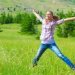 Happy girl jumping on the field - Stok fotoğraf