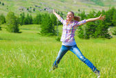 Happy girl jumping on the field — ストック写真