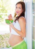 Pregnant woman eating fruits — Stock Photo