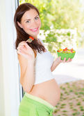 Happy pregnant woman eating — Stock Photo