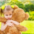 Stock Photo: Sad girl with teddy bear