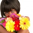 Black female smelling flowers — Stock Photo