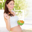 Pregnant woman eating salad — Stock Photo