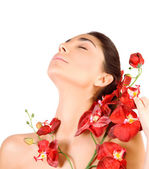 Beautiful woman with red orchid flowers — Stock Photo