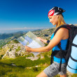 Woman on the mountain watching in map — Stock Photo