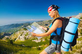 Woman on the mountain watching in map — Stockfoto