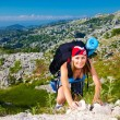 Teen girl climb on mountain - Stock Photo