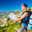 Cute girl in mountains looking to map — Stock Photo #23474128