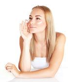 Cute female applying facial cream — Stock Photo