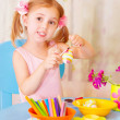 Baby girl painting Easter eggs - Stock Photo