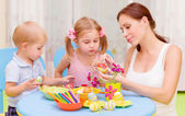 Little kids with teacher painted Easter eggs — Stock Photo