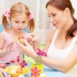 Baby girl with mother paint Easter eggs - Stock Photo