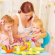 Children with mother paint eggs - Stock Photo