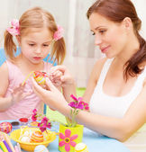 Baby girl with mother paint Easter eggs — Stock Photo