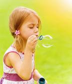 Baby flicka blåser såpbubblor — Stockfoto