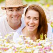 Happy couple on daisy field — Stock Photo