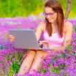 Cute woman with laptop outdoors — Stock Photo