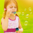 Baby girl blowing soap bubbles — Stock Photo #26155135