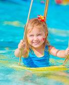 Happy girl on water swing — Stock Photo